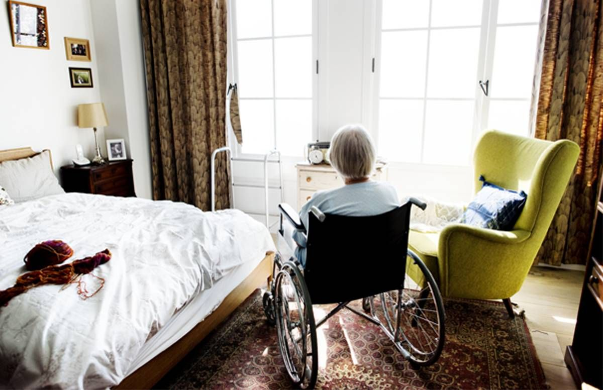 Woman in a wheelchair staring out of the window of her living area.
