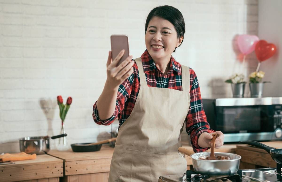 Woman cooking while watching a screen.