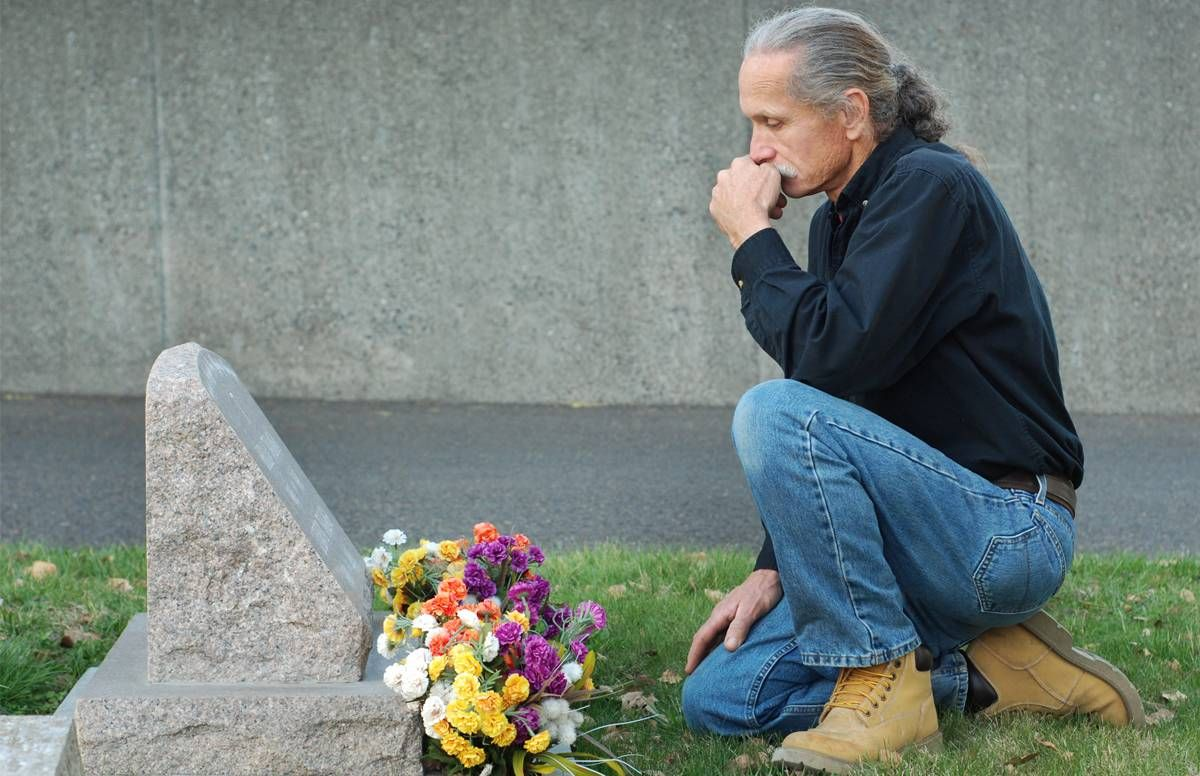 man kneeling alone at gravesite