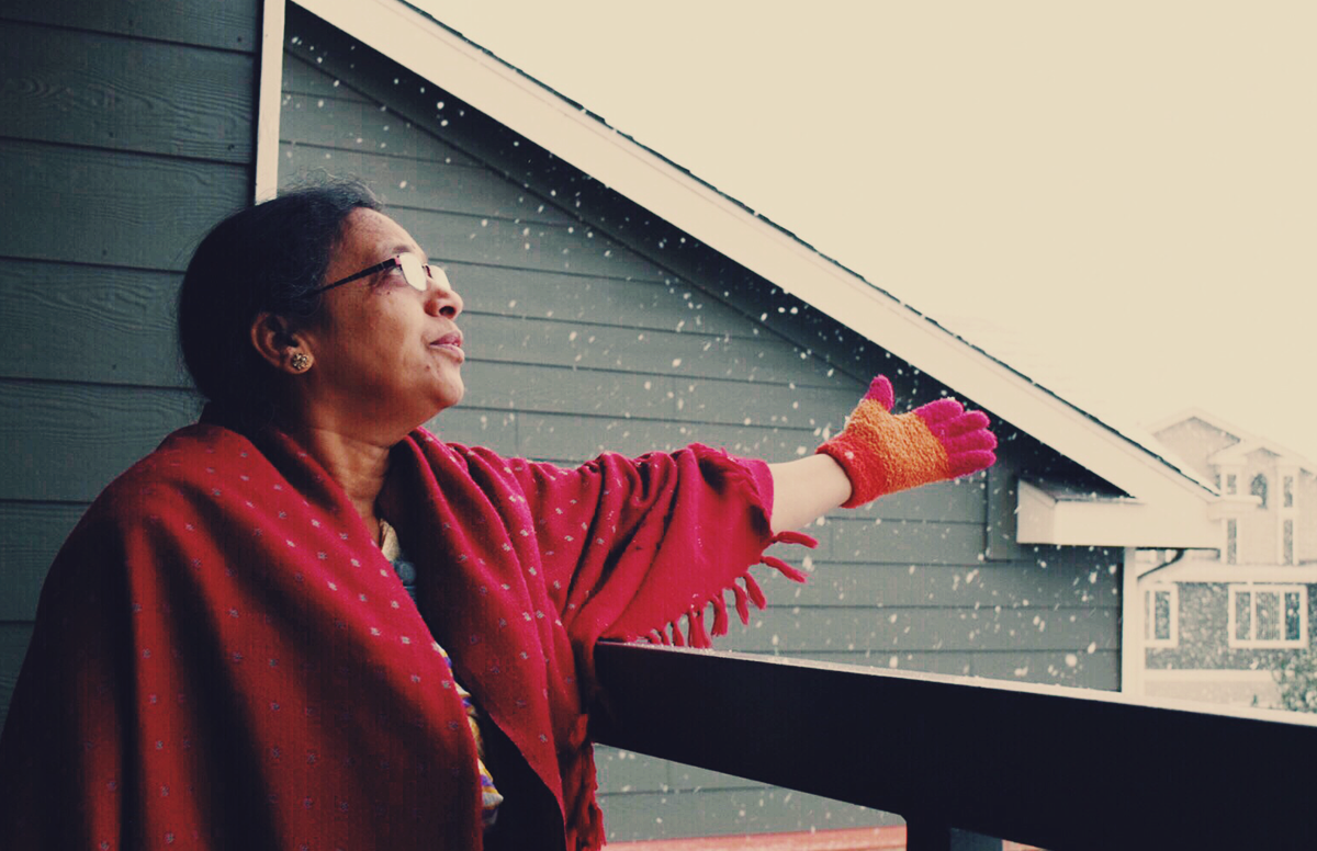 Woman touching snow on a patio