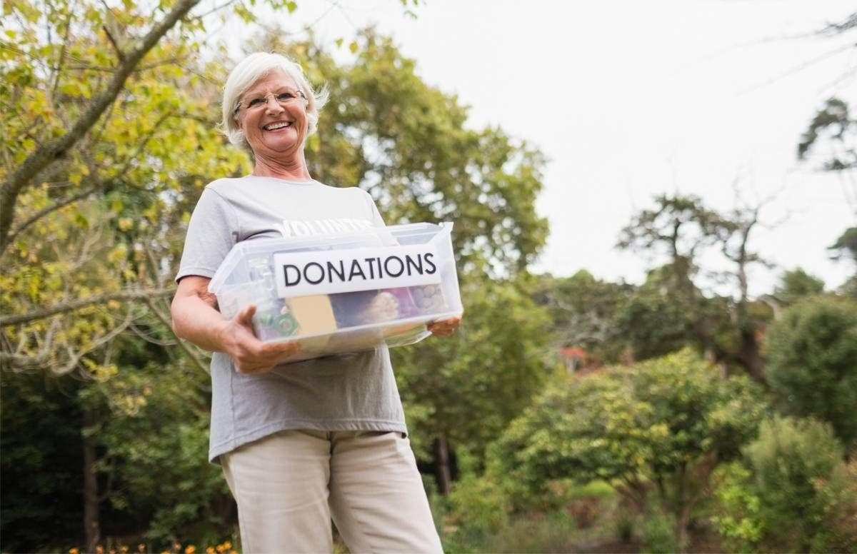 Volunteer holding a Donations box.