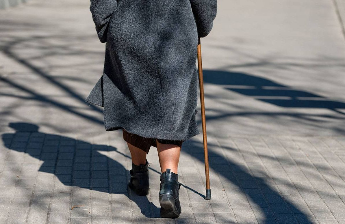 On a sunny day a old woman walking down the street with walking stick. The woman's shadow is visible on the sidewalk. View from the back.