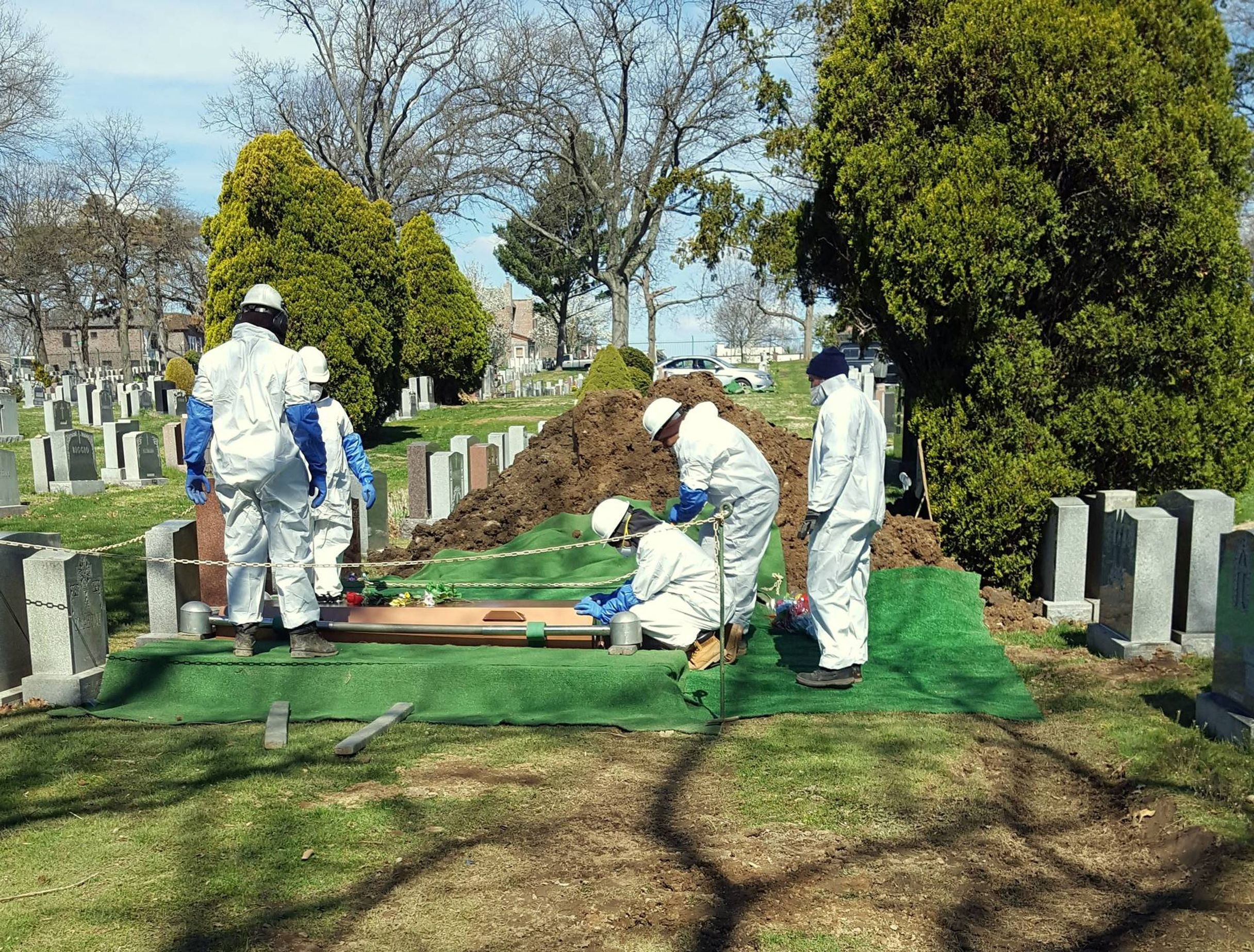 Gravediggers in protective clothing at a recent New York City-area funeral