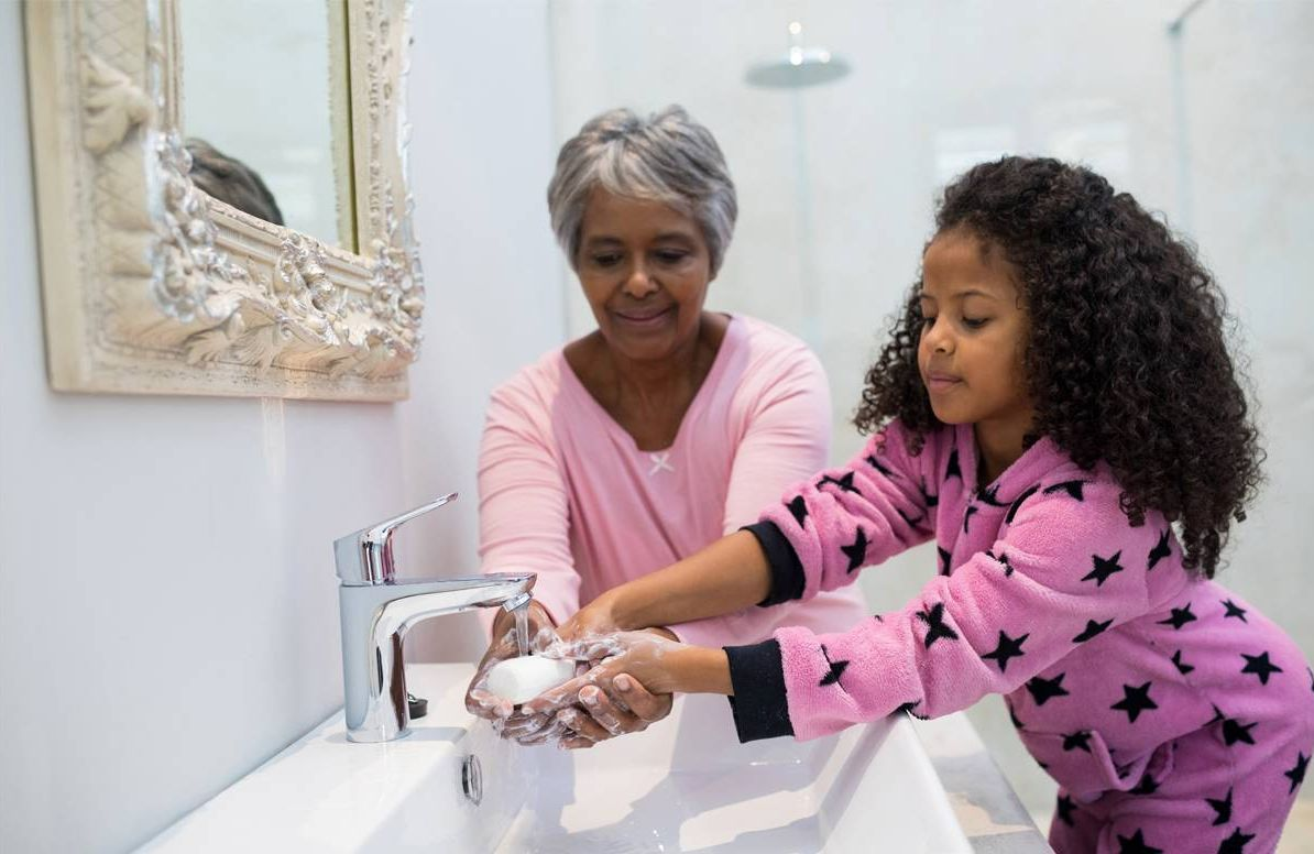 Grandmother helping granddaughter wash hands