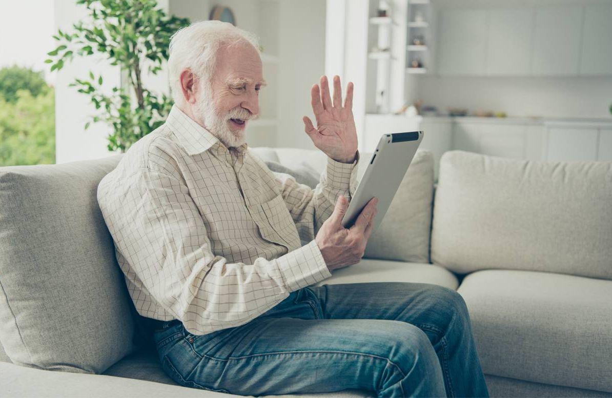 man waving at his tablet