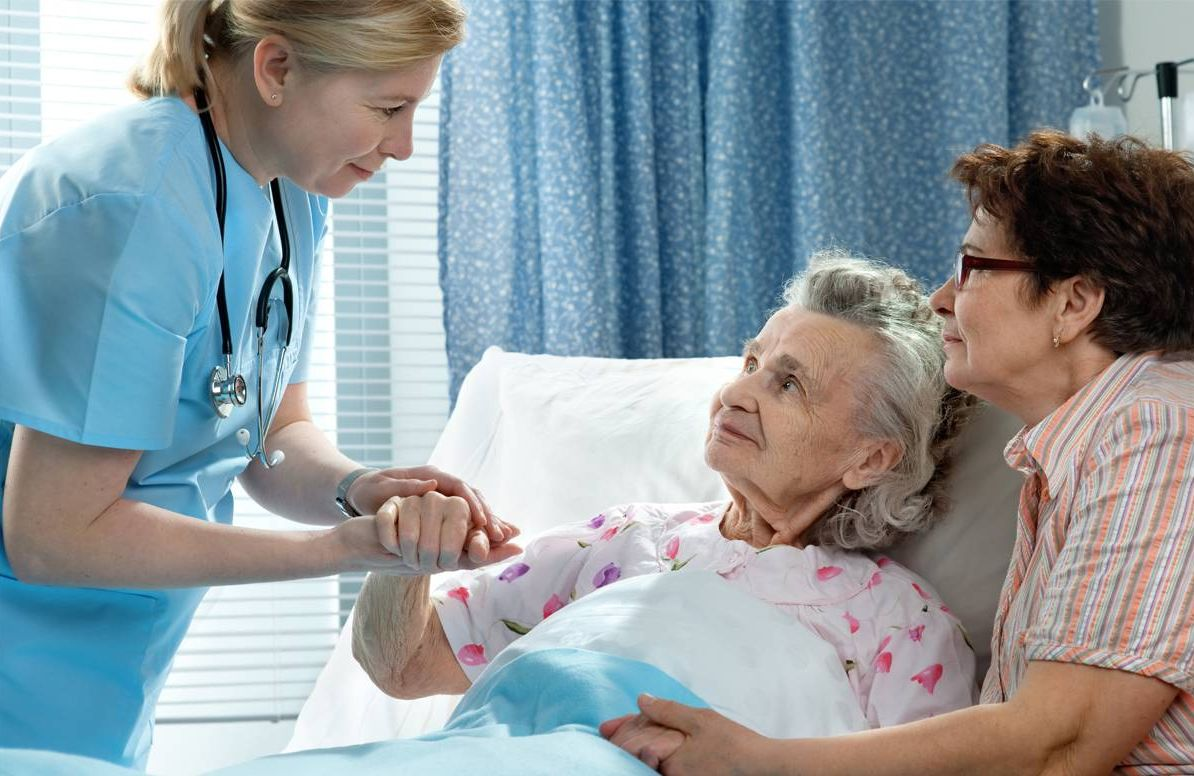 Older adult patient with daughter and doctor