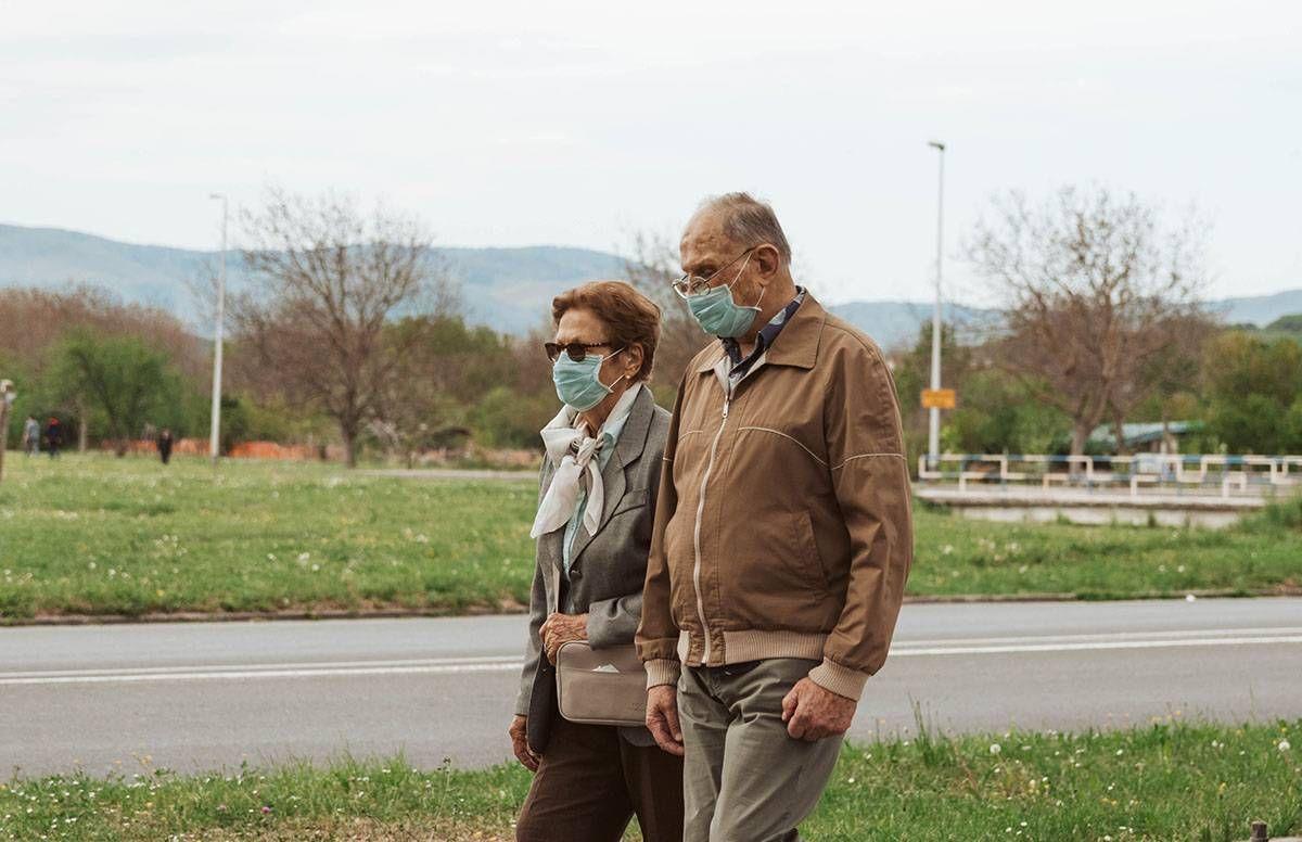 Older couple walking with masks