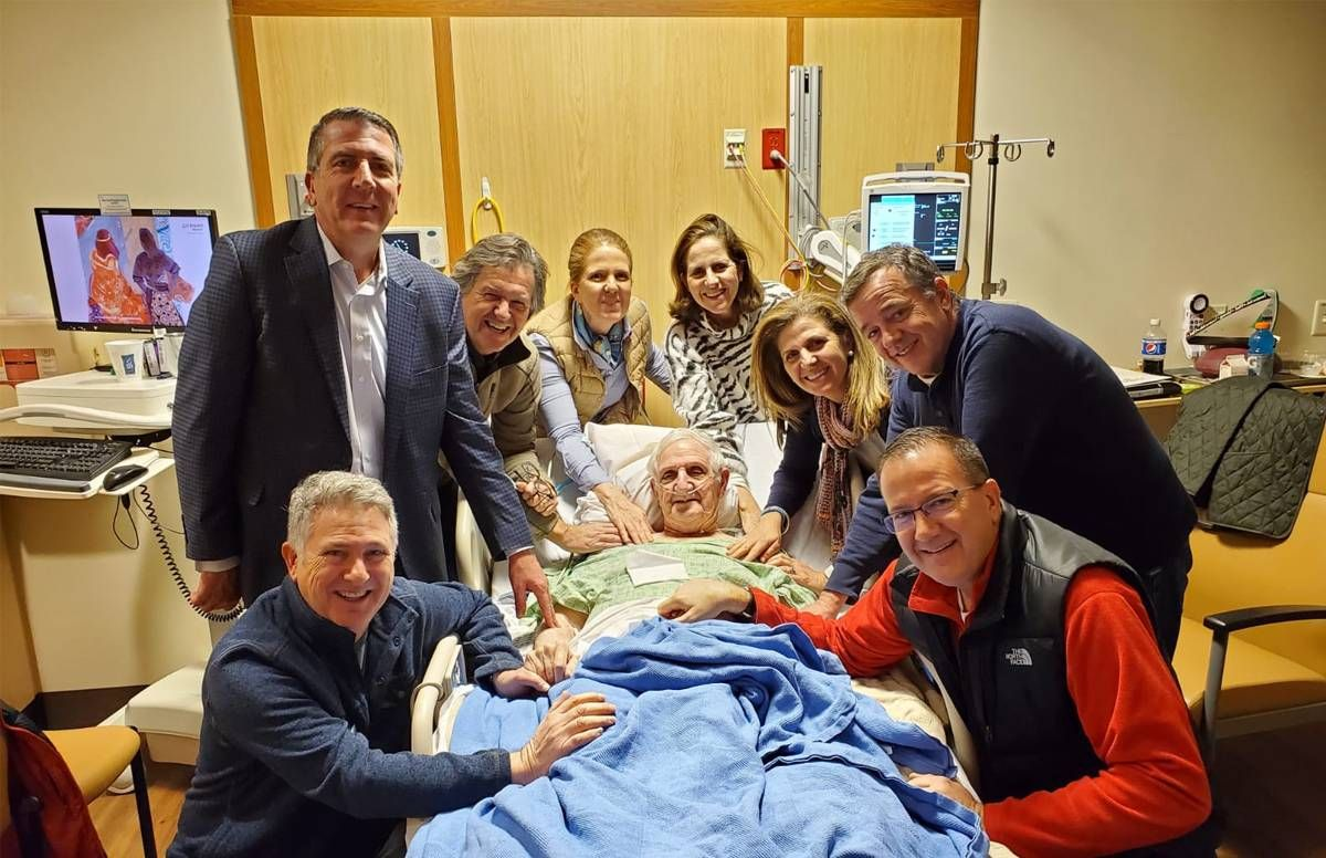 Brian Owen (third from left) and his siblings hired two private home health staff to care for their father (center) near Boston while he waited for a bed in a hospice