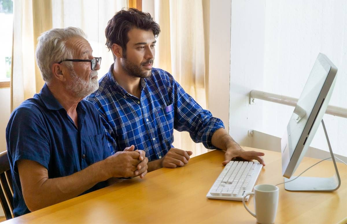Middle-aged man helping his dad with finances