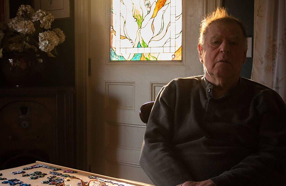 older man sitting at table at home