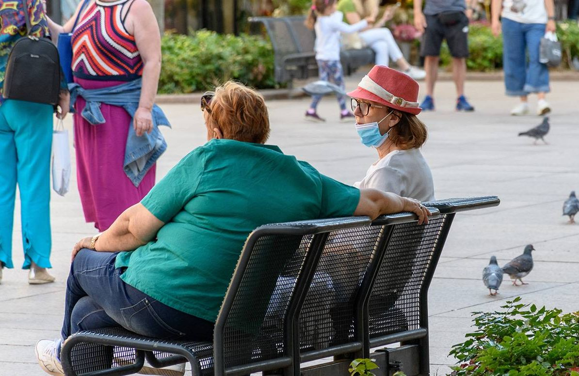 Two people on bench, one with COVID-19 mask around her chin