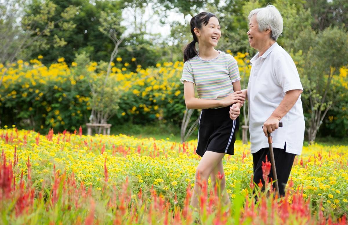 older woman and younger woman on a walk in a field of flowers