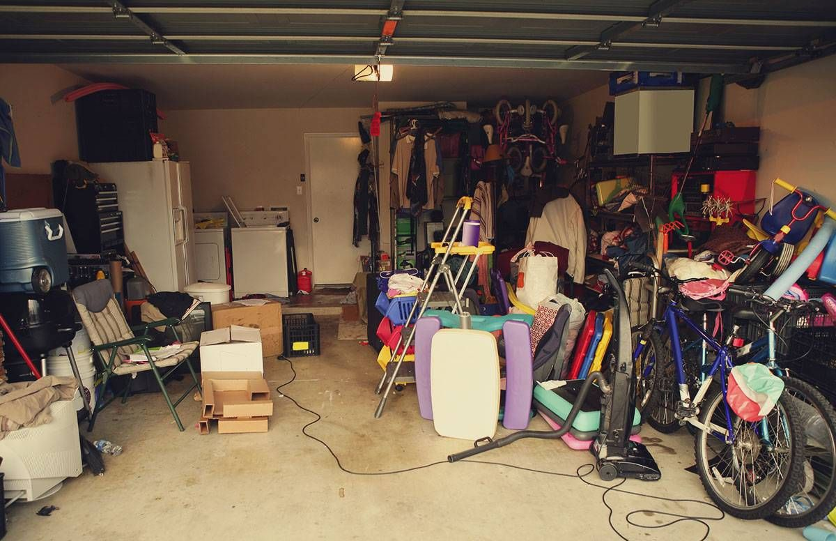 a cluttered garage with bicycles and items