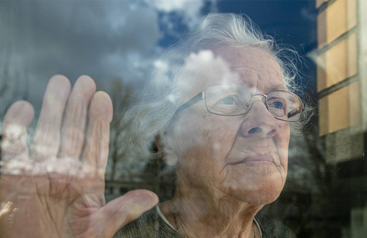 older person looking out window