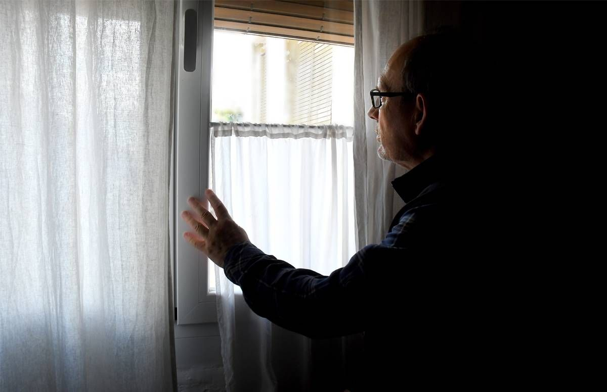 man looking out of the window of his dark home