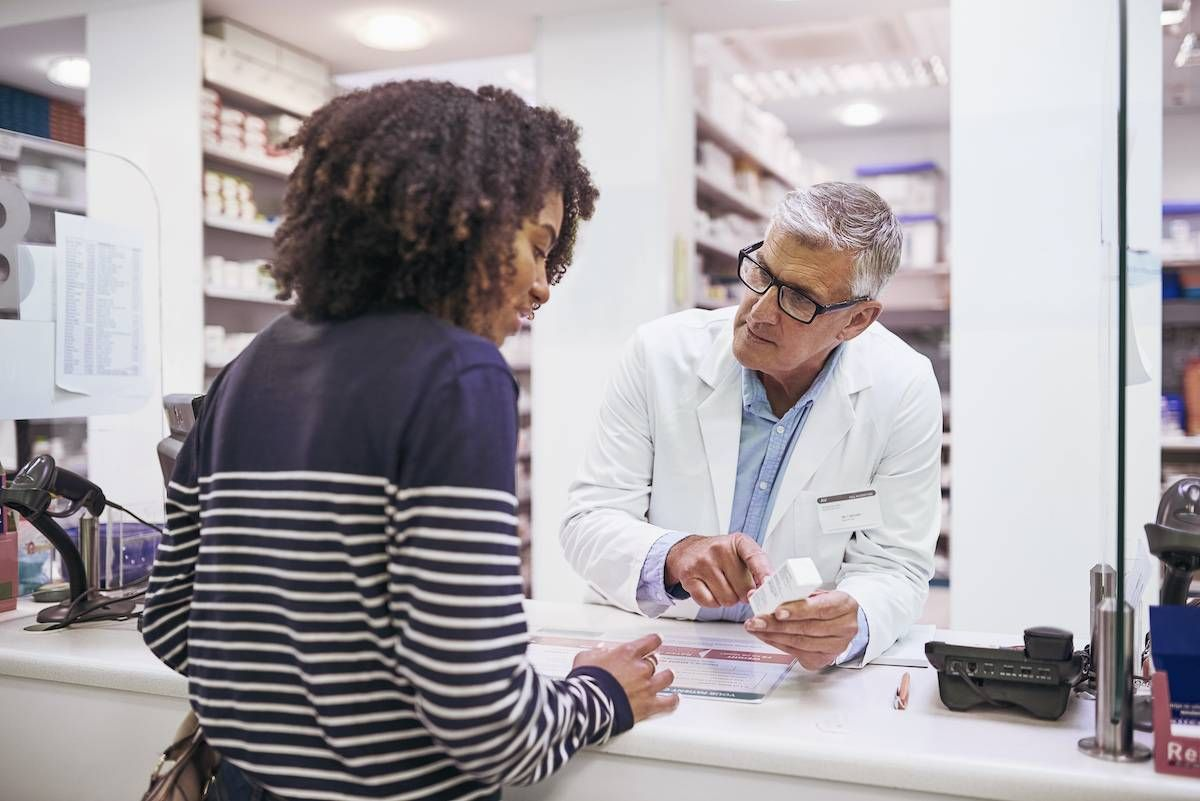 Shot of a dedicated mature male pharmacist giving a customer prescription meds over the counter