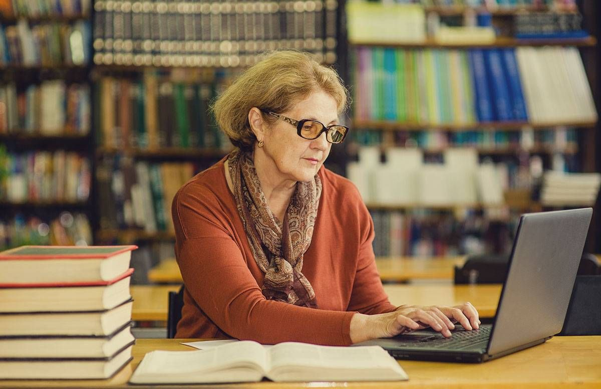 a middle-aged woman in a library, working on a laptop
