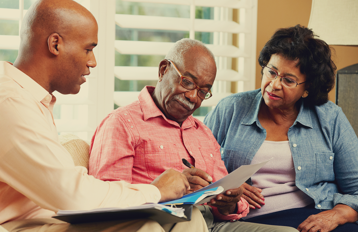 a middle aged couple in their living room meeting with a financial adviser