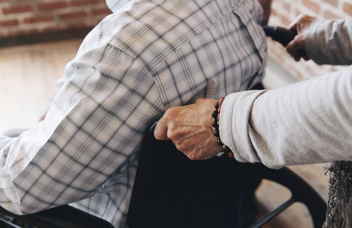 caregiver pushing her husband's wheelchair
