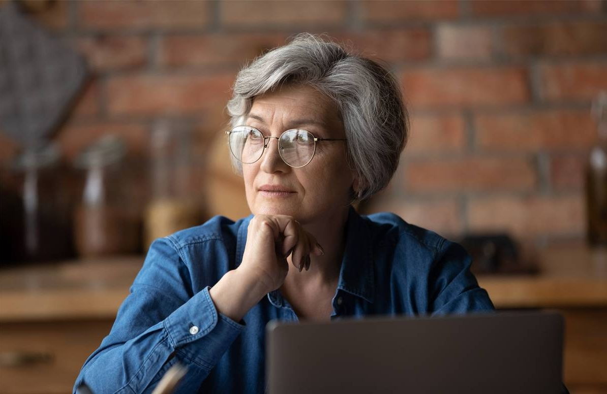 woman looking pensive at computer