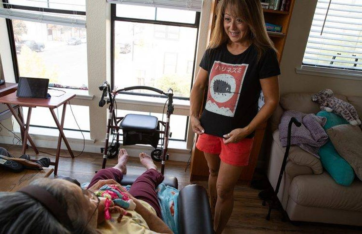 Eiko Oka 83, reads the Japanese saying printed on her daughter June's shirt inside their apartment in San Jose's Japantown