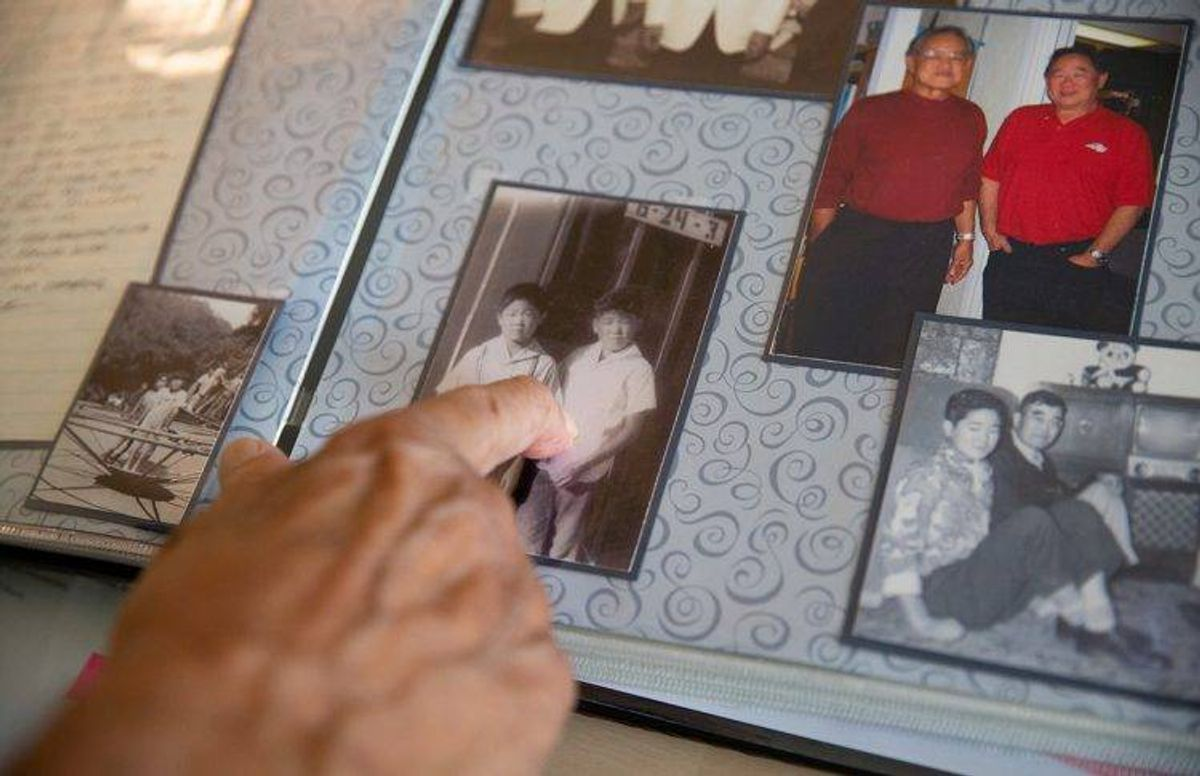 James Oka points to a photo of himself at age seven taken at the Heart Mountain Relocation Camp in Wyoming. Yasuhara made several family scraps books to help her parent's recall their past.