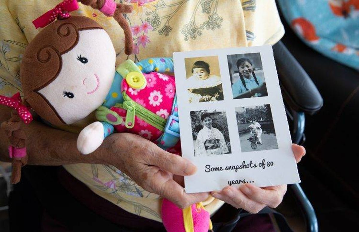 Eiko Oka holds photos of herself taken in Japan and the U.S. Her daughter June Yasuhara made this card to celebrate her 80th birthday.