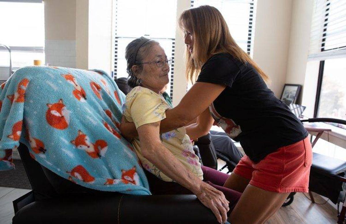 June Yasuhara helps her mom Eiko Oka, 83, get into her wheelchair.