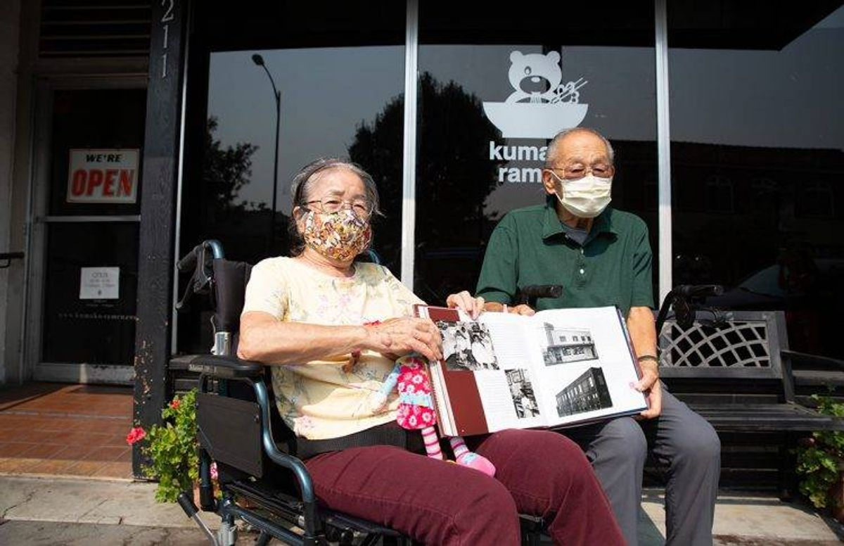 James and Eiko Oka sit in front of the building, once a coffee shop where they first met. A historical book about San Jose's Japantown features a photograph of Eiko Oka at the coffee shop.