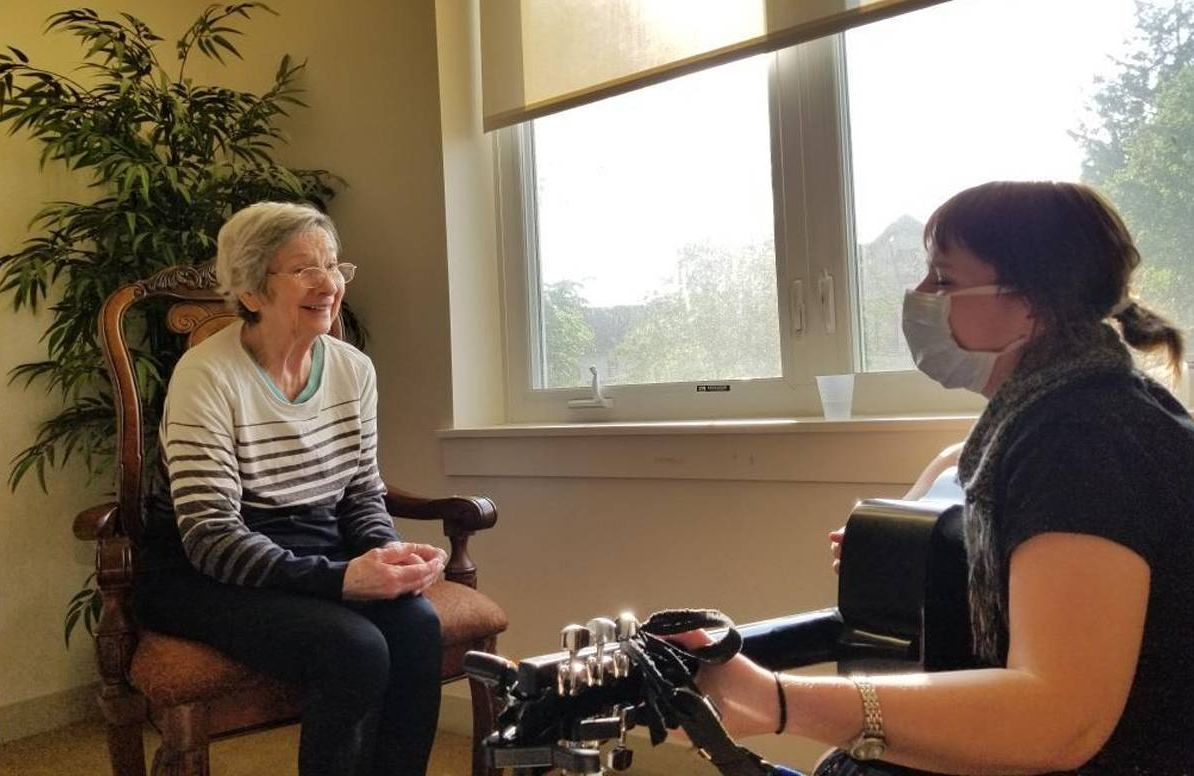 Music therapist Kimberly Williams plays guitar for patient Elaine Lego