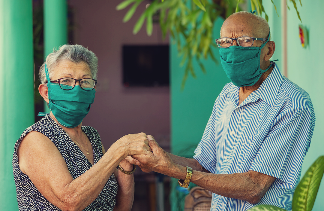 older couple holding hands while wearing masks