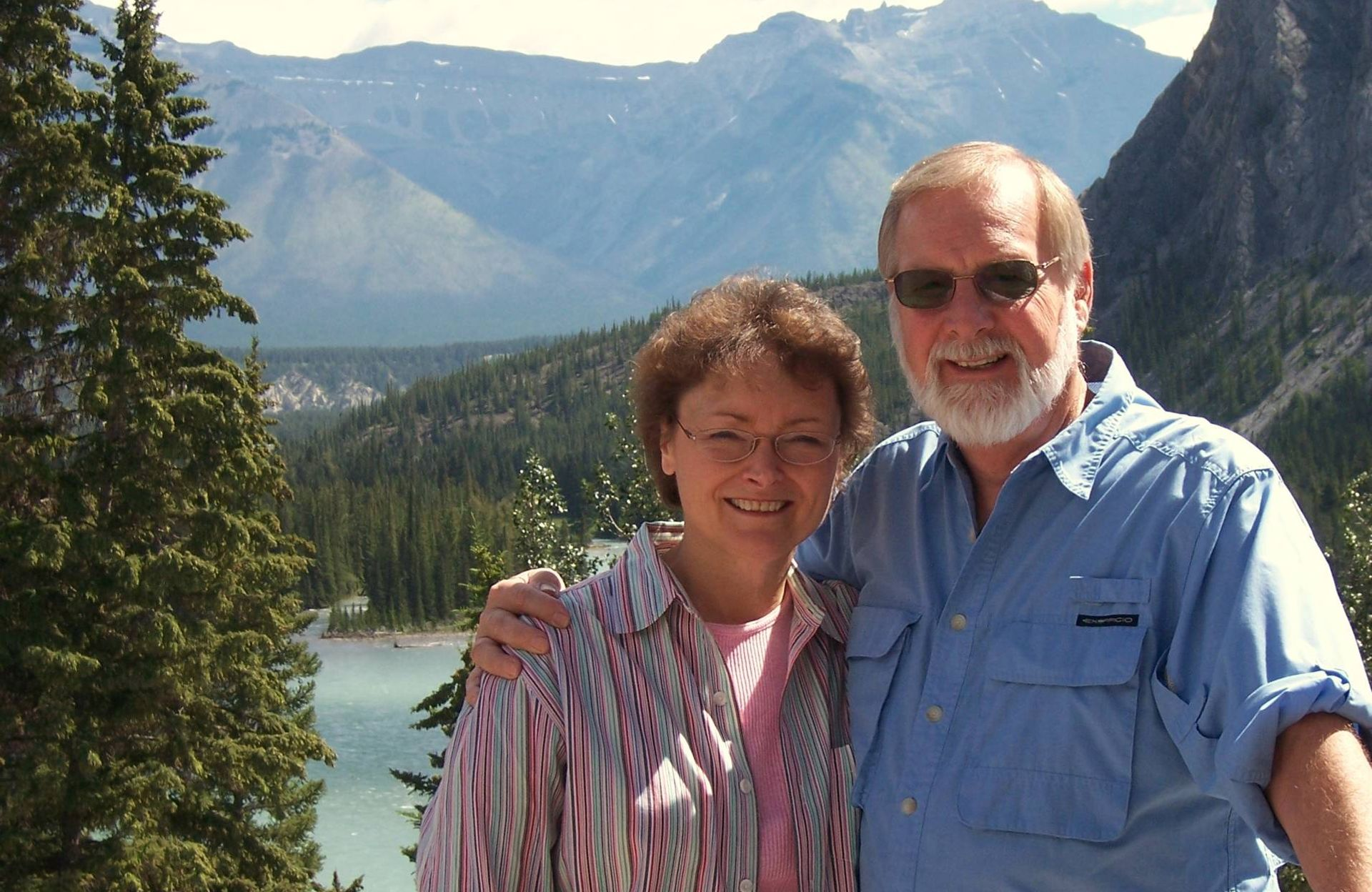 David and Linda stand in front of a picturesque scene of a lake and mountains.