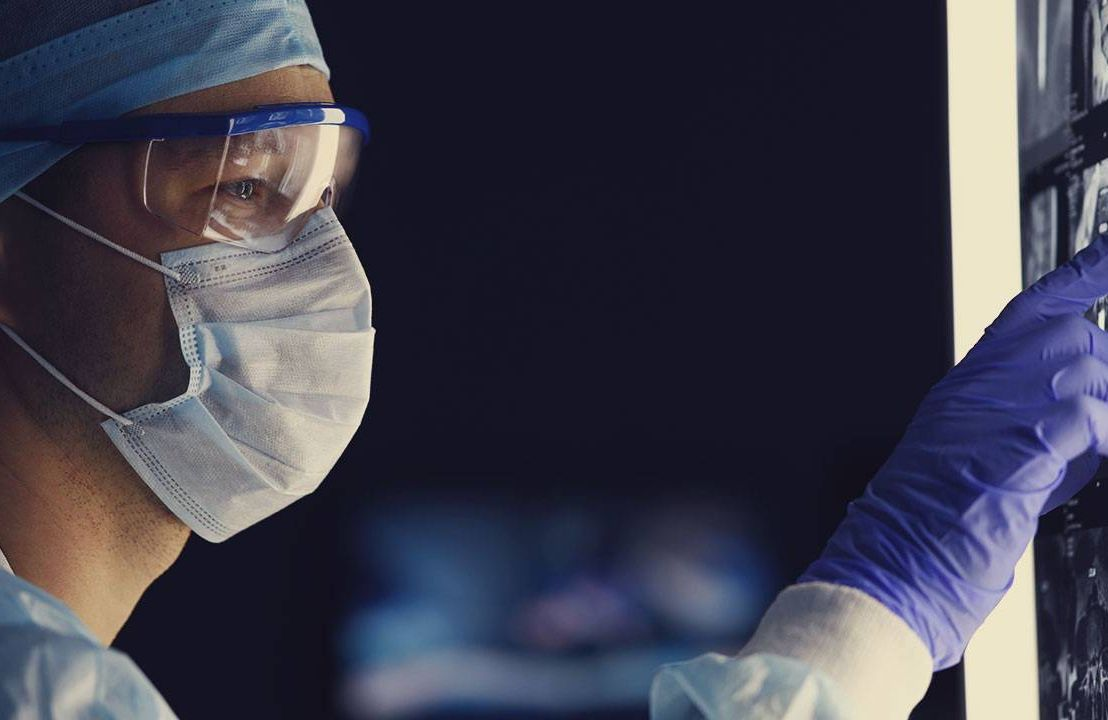 a doctor in a mask looking at a test tube