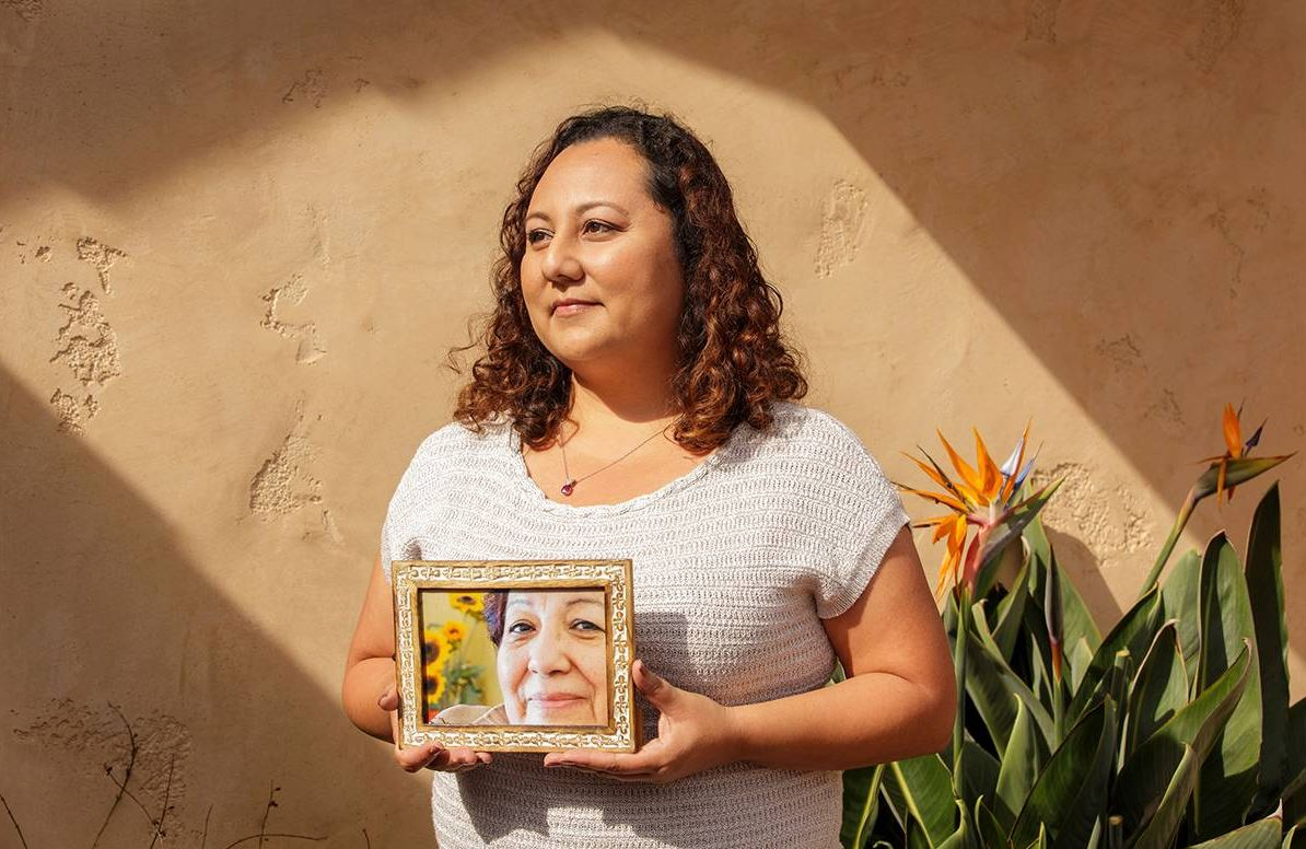 Michelle Rios holds a photo of her late mother Maria Elena Nuñez.