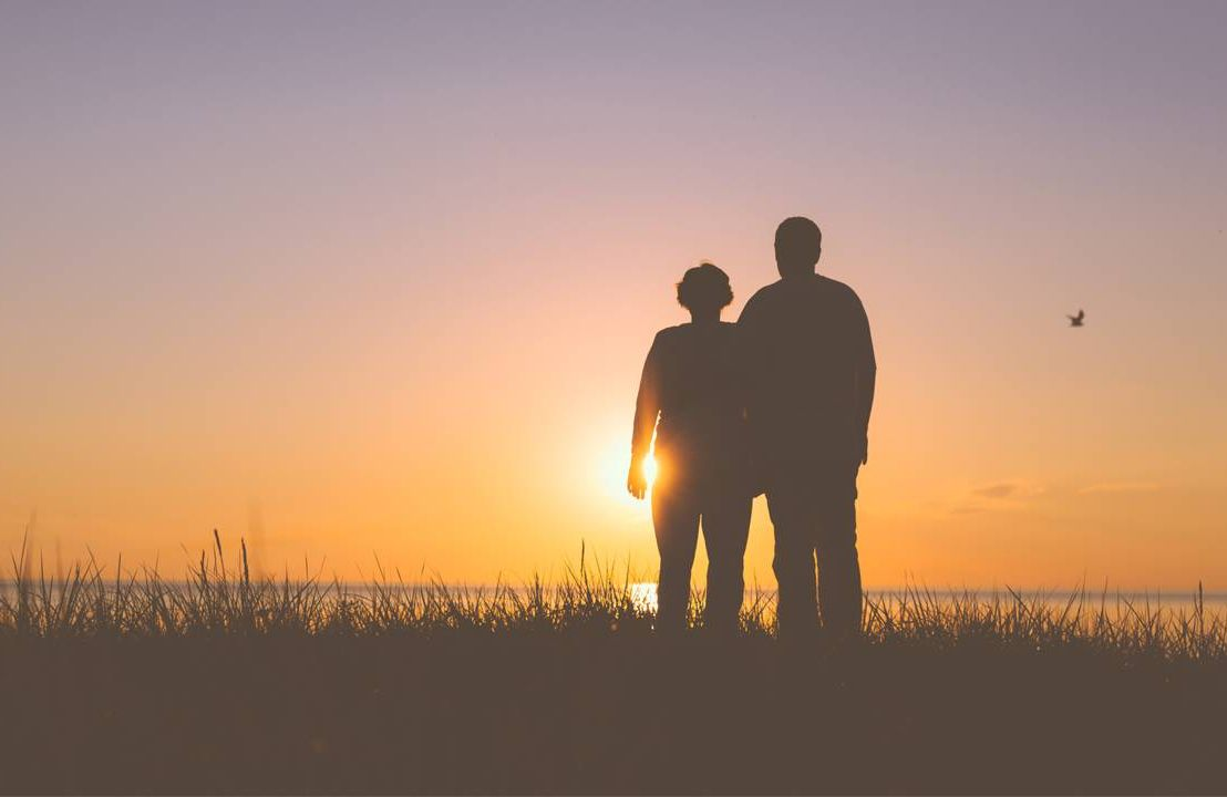 couple watching the sunset in shadow, end a marriage, next avenue