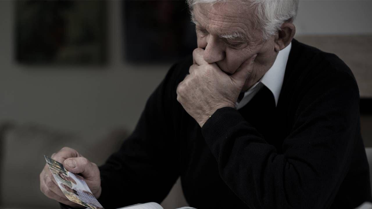 man looking at photos, Next Avenue, holiday depression