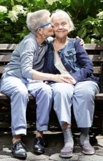 Cindy kissing Helen's face on a park bench