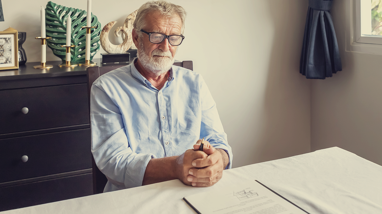 man sitting at his kitchen table, preparing to sign legal documents.