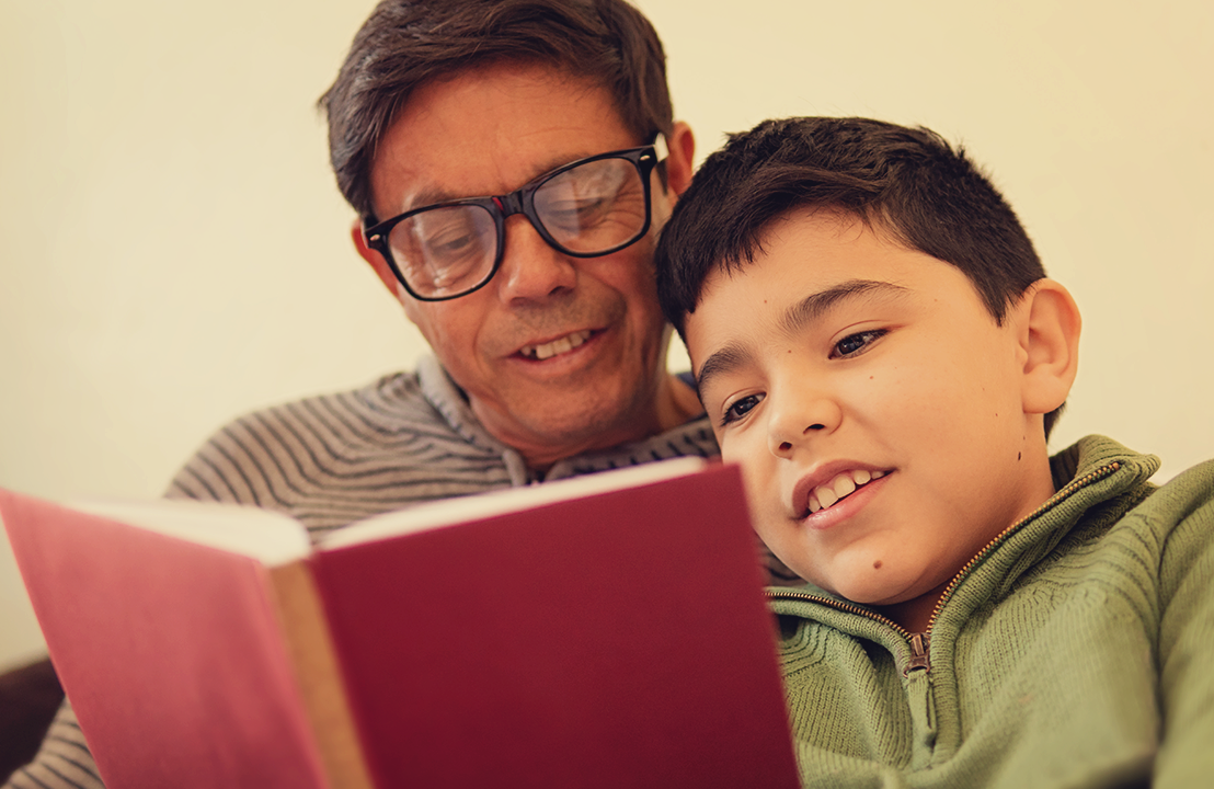 A grandfather reads a book with his grandson