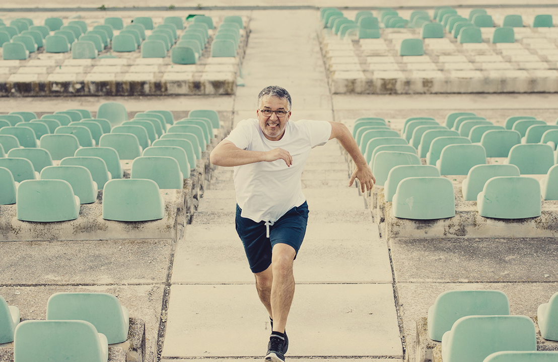 a middle-age man running up a series of stairs in an empty stadium
