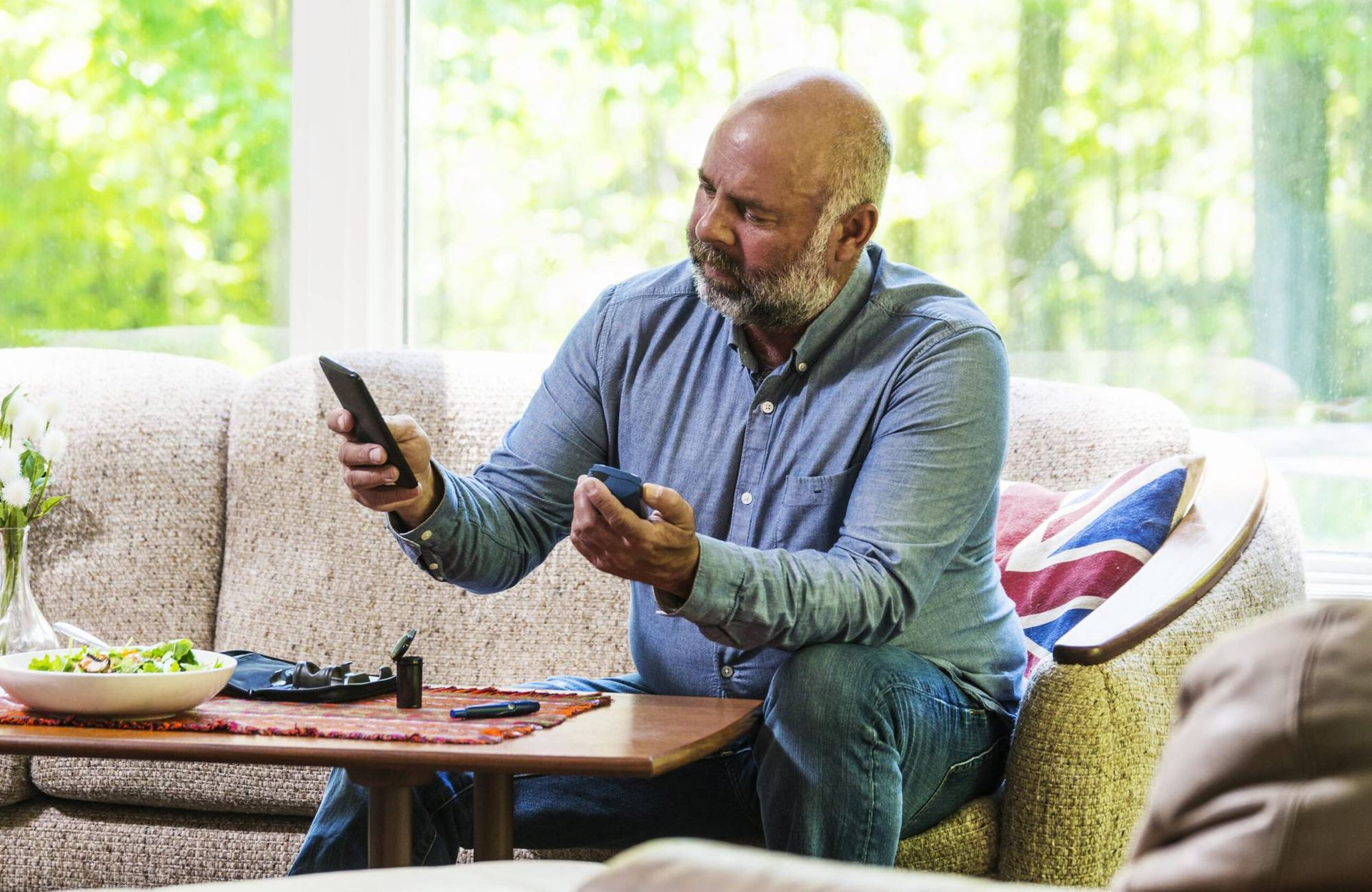 """Mature diabetic man testing his blood sugar and using a smartphone, """"How Can I Manage My Diabetes?"""""""
