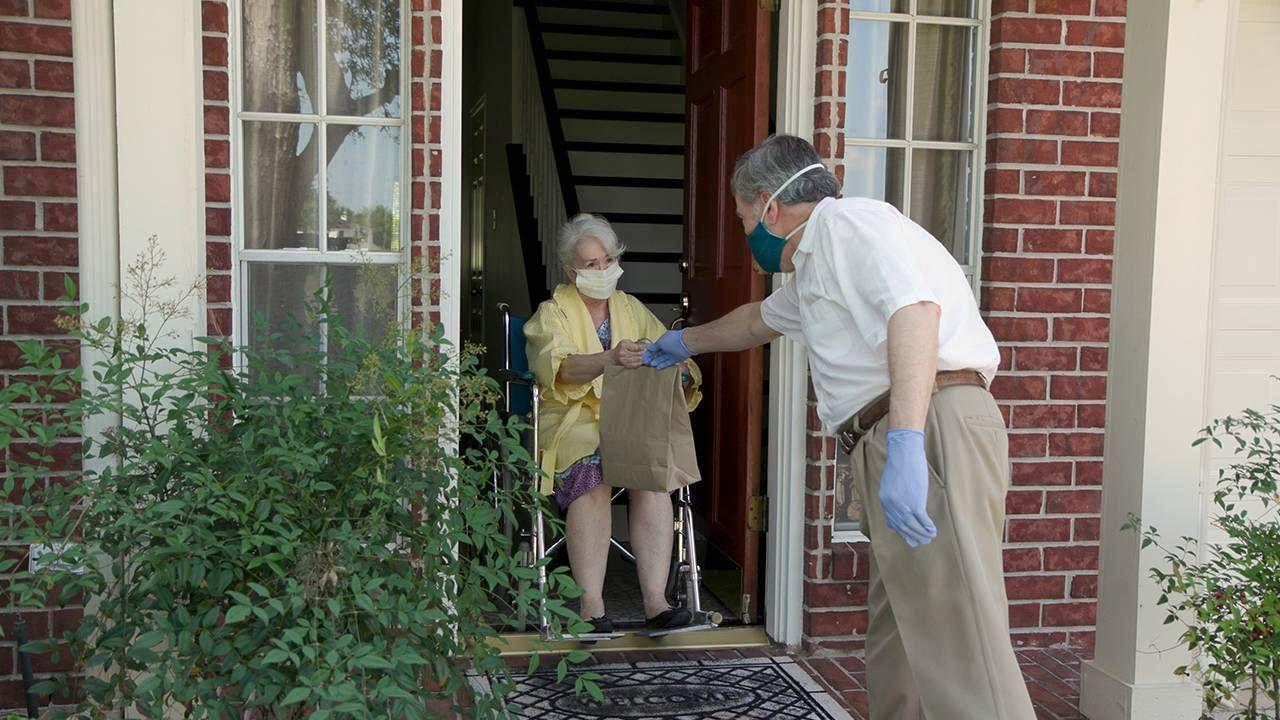Older adult receiving groceries at her front door, COVID-19 vaccine