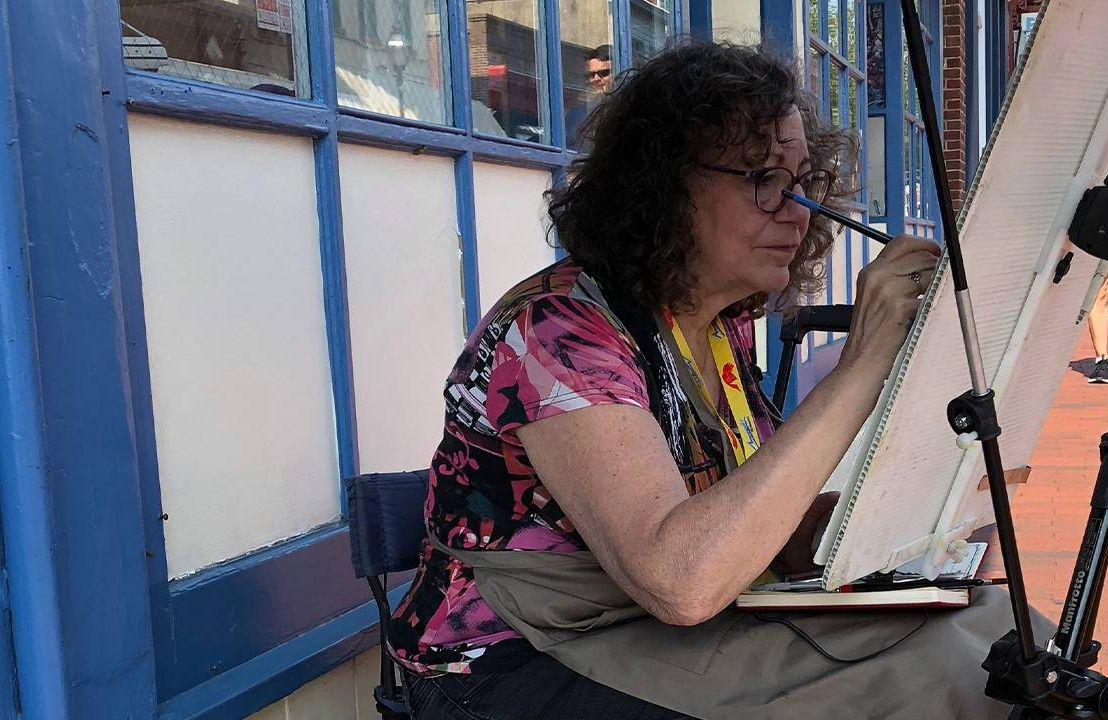 Woman painting on the street, Medicare recipients