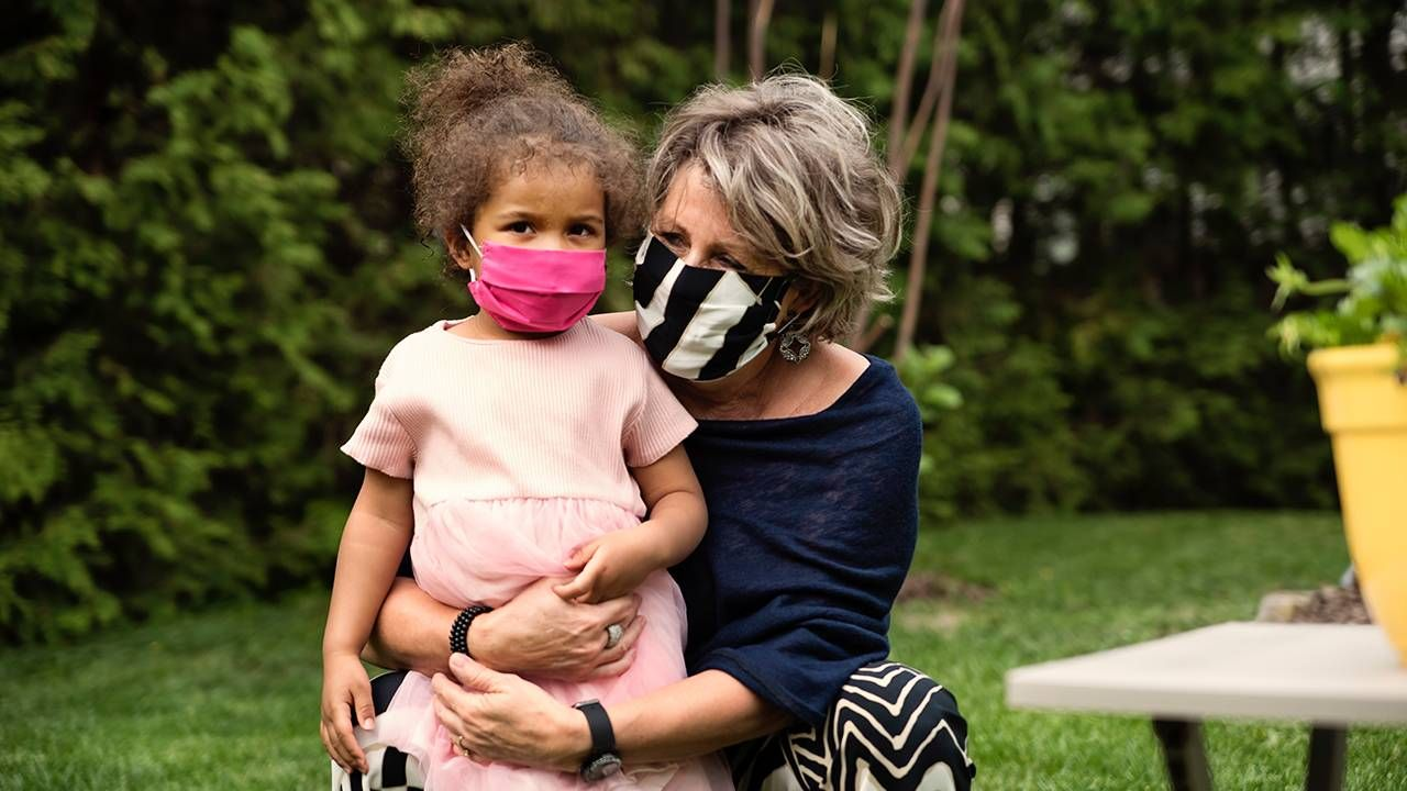 Grandmother and grandchild outside wearing face masks