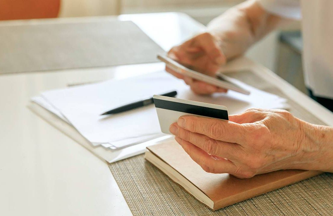 Woman holding credit card paying bills, debt trends