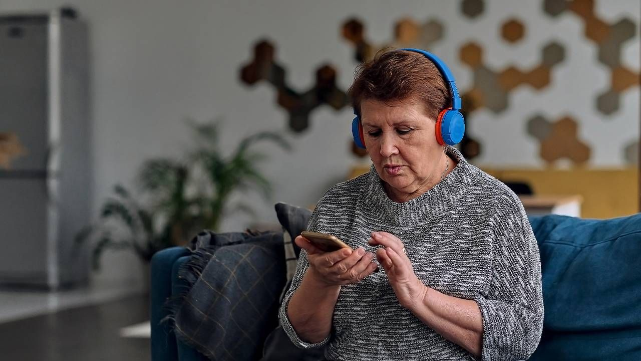 A woman listening to an audiobook with headphones, next avenue, audiobook, turn up audiobooks