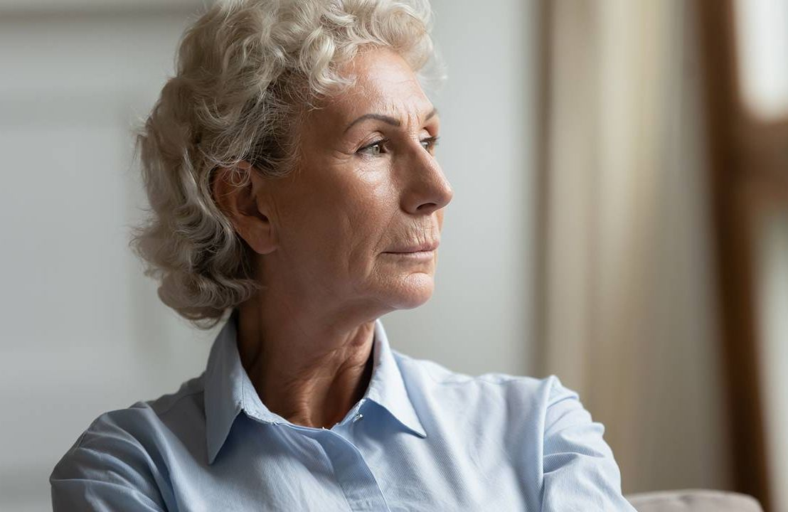 Woman in collared shirt looks out the window, workplace bias training, agism, Next Avenue, age bias