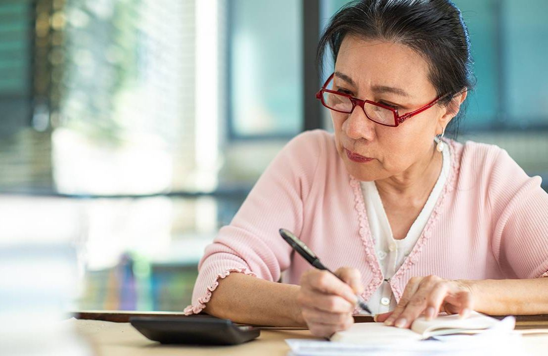 Older woman filling out a 2020 tax return, taxes, unemployment benefits, Next Avenue