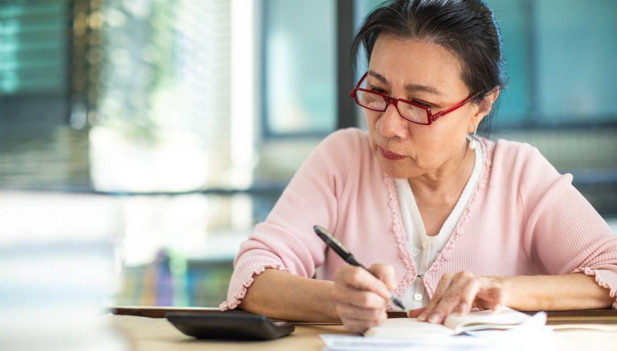 Older woman filling out a 2020 tax return, taxes, unemployment benefits, Next Avenue