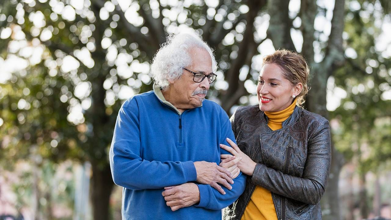 A father and his adult daughter walking together outside, caregiver, Next Avenue, helping an aging parent